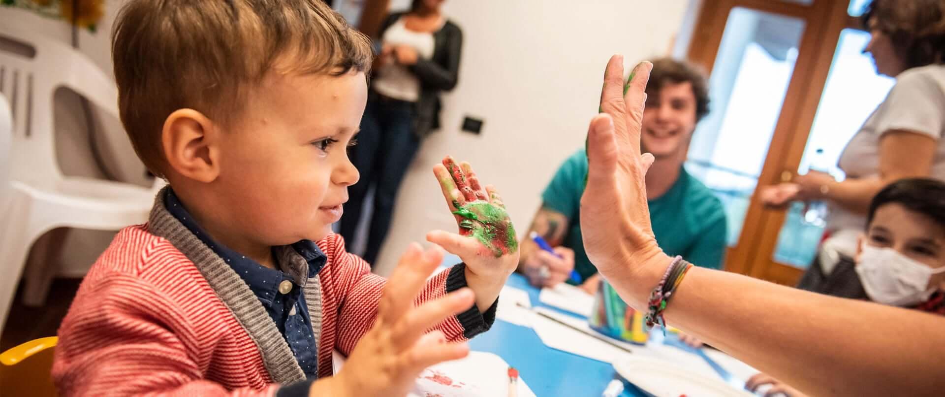 Bambino con mano sporca di colore