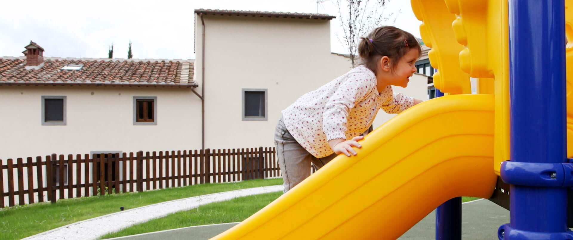 Bambina che gioca sullo scivolo