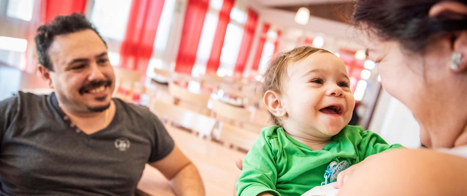 Bambino sorridente tra le braccia della mamma